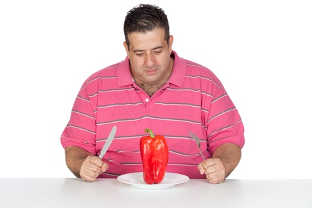 Fat man eating a red pepper isolated on white background photo