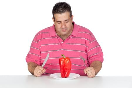 willpower: Uomo grasso mangia un peperoncino rosso isolato su sfondo bianco