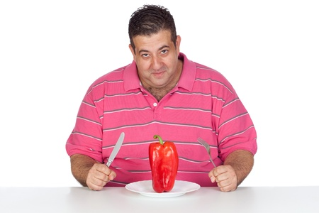 Fat man eating a red pepper isolated on white background Stock Photo