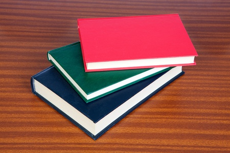 books on a wooden surface: Three hardcover books on a wooden surface