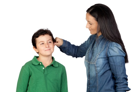 punish: Mother pulling her childs ear for being naughty isolated on white background
