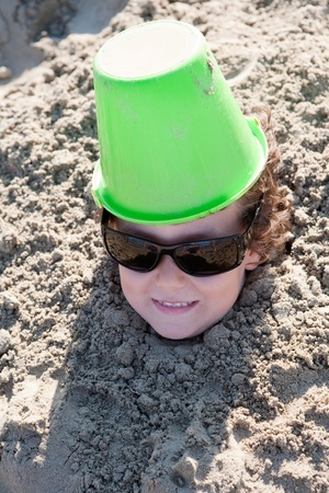 bury: Small child buried in the sand of the beach with sunglasses
