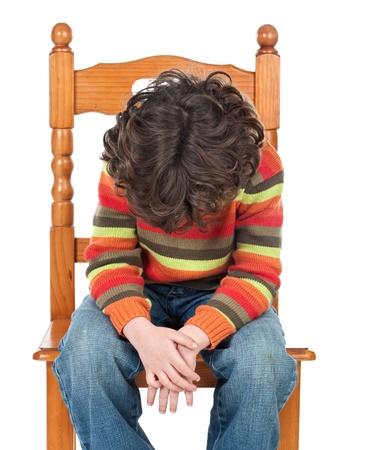 alicaído: Niño triste sentado en una silla aislados sobre un fondo blanco