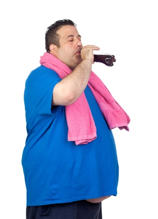 Fat man in the gym drinking cola isolated on a white background photo