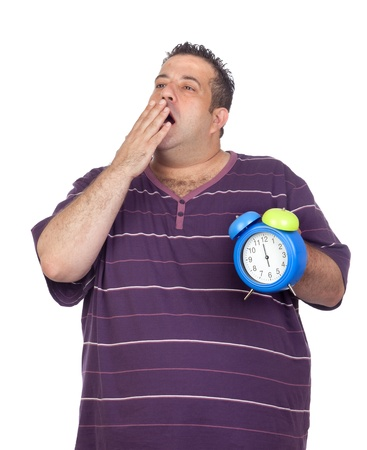 Fat man with a blue alarm yawning clock isolated on white background photo