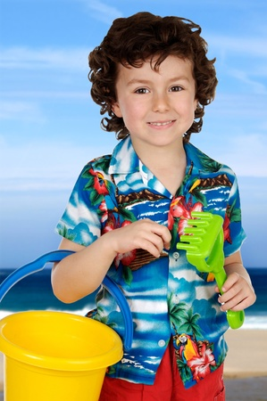 Adorable boy playing in the beach with beach toys photo