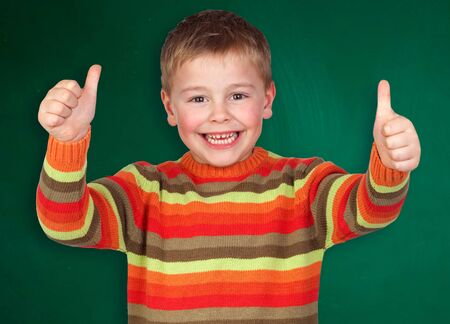 Happy student child saying Ok isolated over green blackboard photo