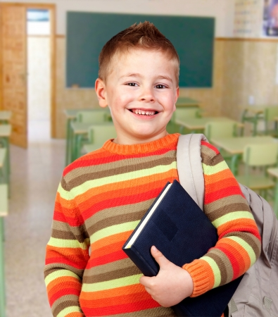 Beautiful child with books and backpack in class photo