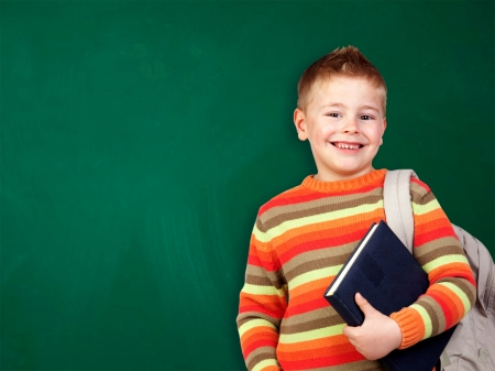 Student child with books isolated over green blackboard photo