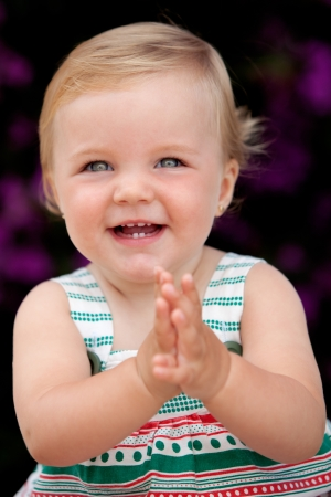 Baby girl clapping with a nice smile on the outside photo