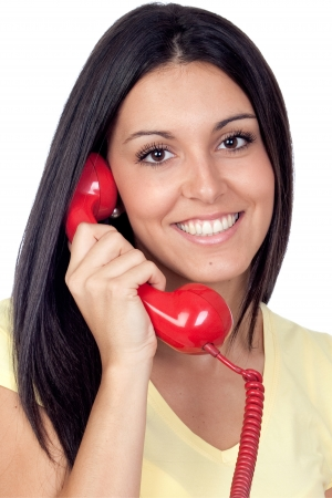 Attractive brunette girl calling with red phone isolated on white background Stock Photo