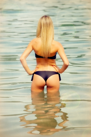 Attractive blond woman on the water with a black bikini photo