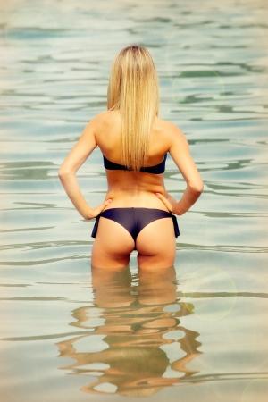 frauenarsch: Attraktive blonde Frau auf dem Wasser mit einem schwarzen Bikini Lizenzfreie Bilder