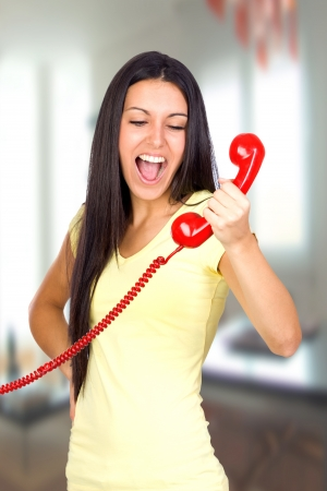 Casual Woman Shouting a Red Phone in the office photo