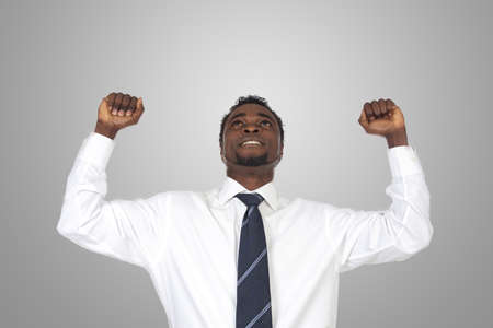 Attractive businessman celebrating a triumph a over grey background photo