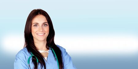 Attractive brunette doctor on blue and white background photo