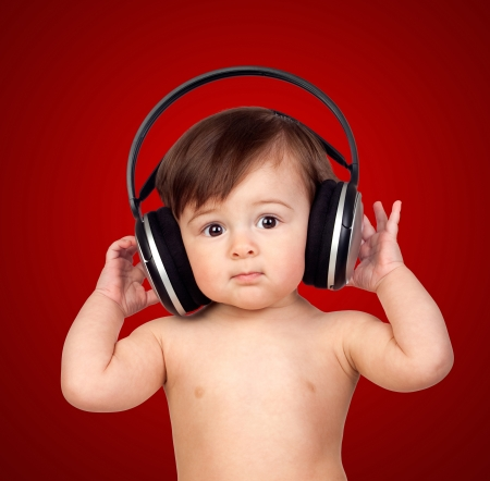 Adorable baby girl with big headphones isolated on red background