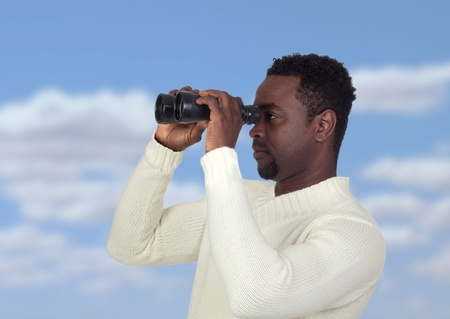 Attractive african man looking through binoculars with a blue sky of background photo