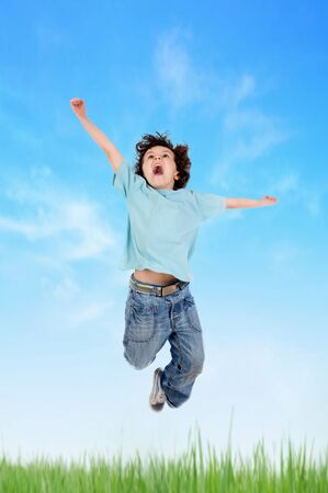 Adorable child jumping on the meadow with blue sky photo