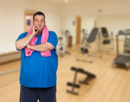 morbidity: Pensive fat man playing sport in the gym