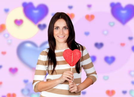 Brunette girl with a big lollipop and a background of colorful hearts photo
