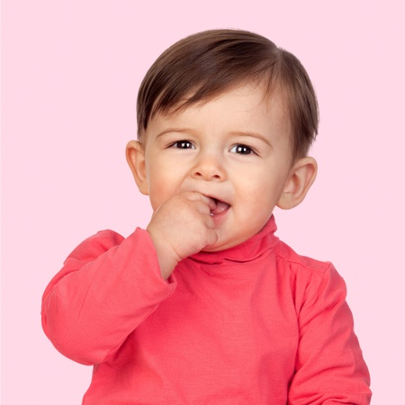 Adorable baby girl with her hand in mouth isolated on pink background photo