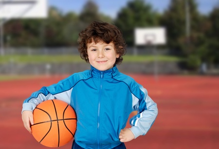 Ni�o adorable que juega al baloncesto en el campo de la cesta photo