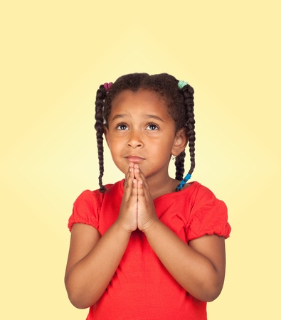 Sad little girl praying for something isolated on a over yellow background photo