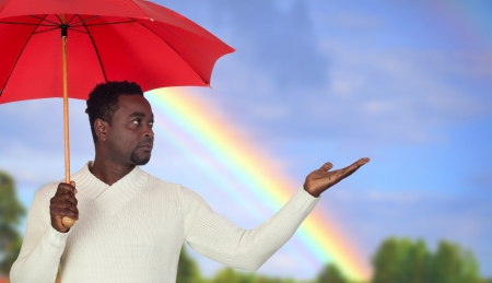 Attractive african man with a red umbrella and a beautiful rainbow Stock Photo - 17341626