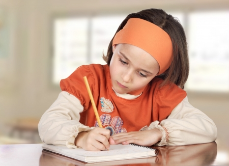 writing letter: Adorable girl studying in the school with a window of background
