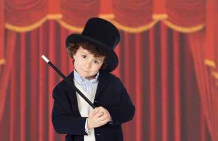 adivino: Vestido adorable ni�o del ilusionista con el sombrero y las cortinas rojas de fondo