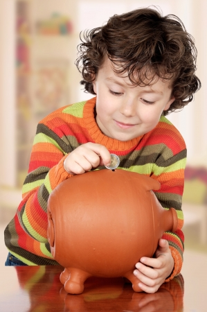 Little boy with his a big piggybank in house Stock Photo - 17405691