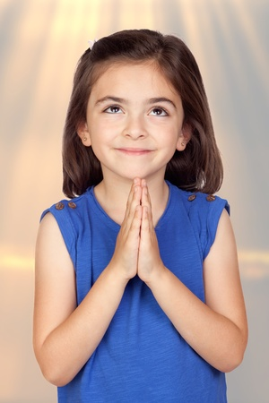 supplicate: Angelic little girl isolated with a ligh of background
