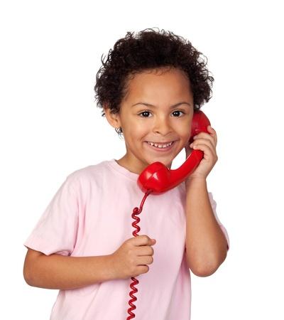 niÑos hablando: Niño latino con el teléfono rojo aislado sobre fondo blanco
