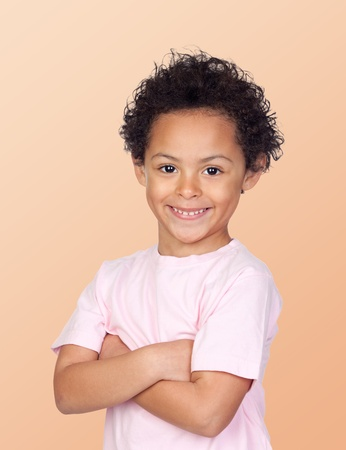 Happy african child with arms crossed isolated on orange background photo