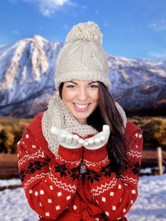Attractive girl throwing a kiss with a snowed mountain of background  photo
