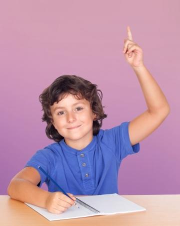 Estudiante niño pidiendo la palabra aislada en un fondo rosado sobre Foto de archivo - 17567864