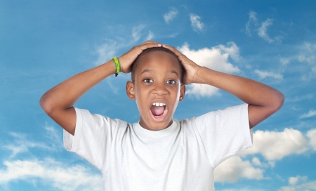madly: Boy shouting madly with his hands over the head with a sky of background Stock Photo