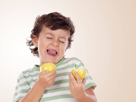 Cute boy eating lemon isolated on a orange background