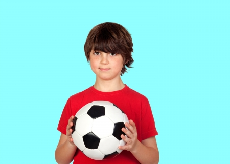 Adorable boy dreaming about being soccer player isolated on blue background photo
