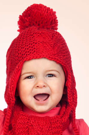 Baby girl with a funny wool red hat isolated on orange background photo