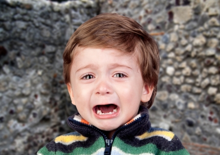 Beautiful baby crying with a wall of background photo