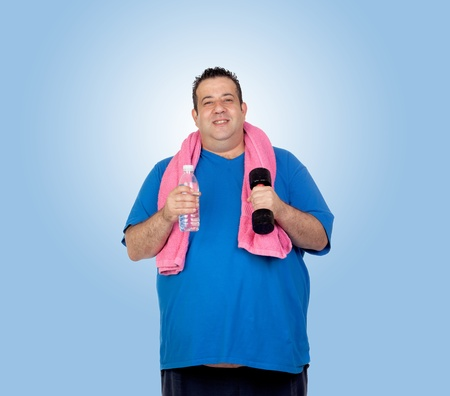 morbidity: Fat man in the gym with a water bottle isolated on a blue background Stock Photo