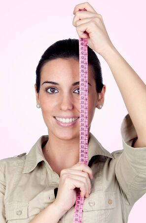 Beautiful girl with tape measure isolated on a over pink background photo
