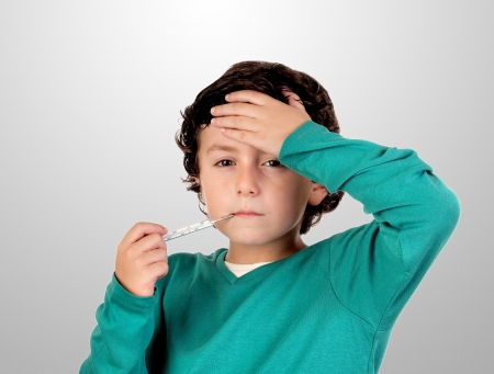 fever: Adorable boy whit thermometer on a over grey background