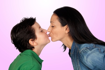 Adorable mother kissing her beautiful son isolated on purple background photo