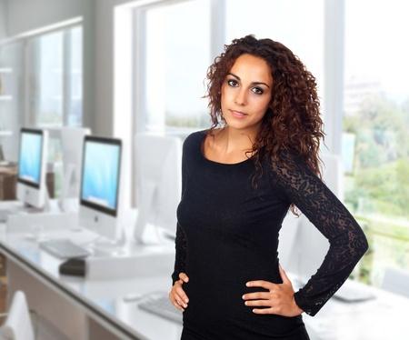 secretaria sexy: Mujer de negocios atractiva con un vestido negro en la oficina