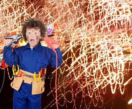 electrocute: Funny little boy simulating electric shock with many sparks Stock Photo
