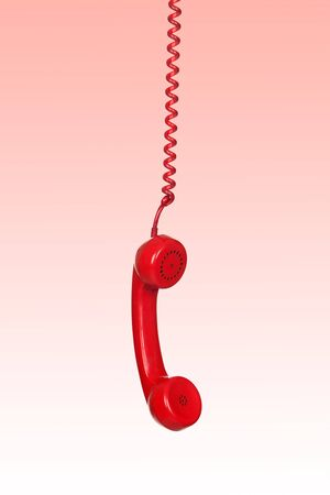 Telephone cable hanging isolated on red background photo