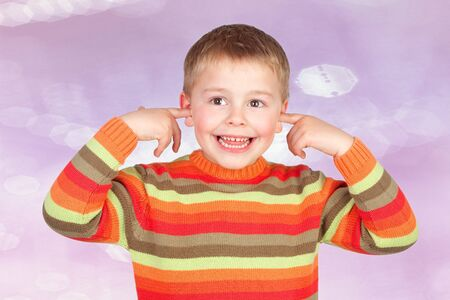 deafening: Funny child covering his ears isolated on a pink background
